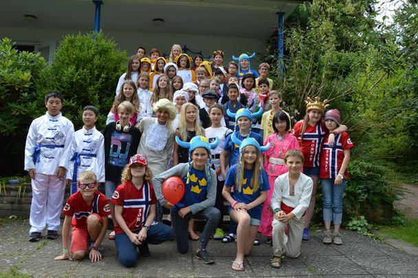 Teilnehmende eines Camps haben sich für das Campfoto in ihren landestypischen Kostümen verkleidet