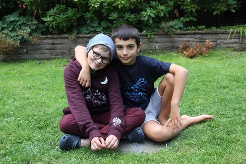 Zwei Jungs sitzen Arm in Arm auf dem Rasen