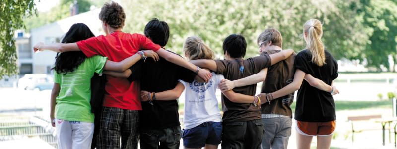 Eine Gruppe von Teilnehmer*innen eines CISV Programms stehen Arm in Arm