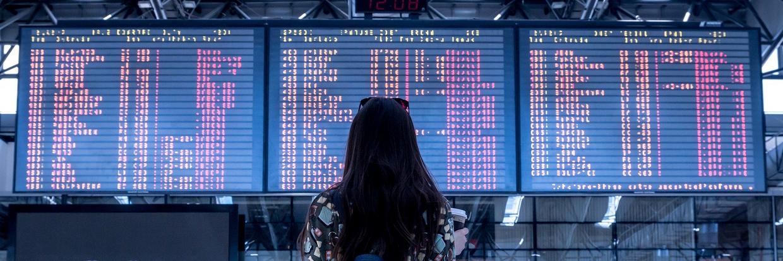 Eine Person schaut auf die Anzeigetafel am Flughafen - Wohin geht deine CISV Reise?